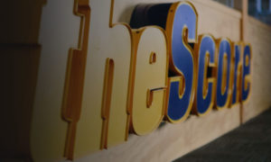 Large, yellow and blue sign reads: theScore